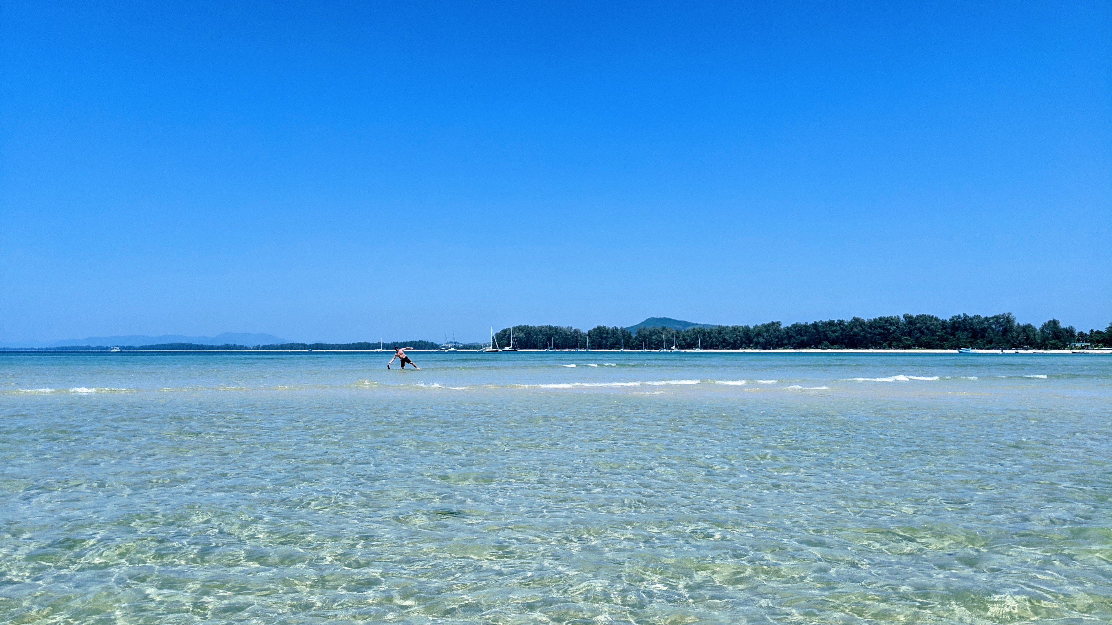 Crystal clear turquoise water of Nai Yang Beach's cove