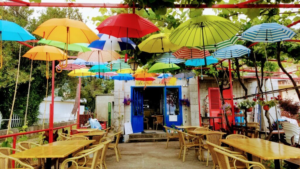 A colorful cafe in the Bay of Kotor filled with umbrellas.